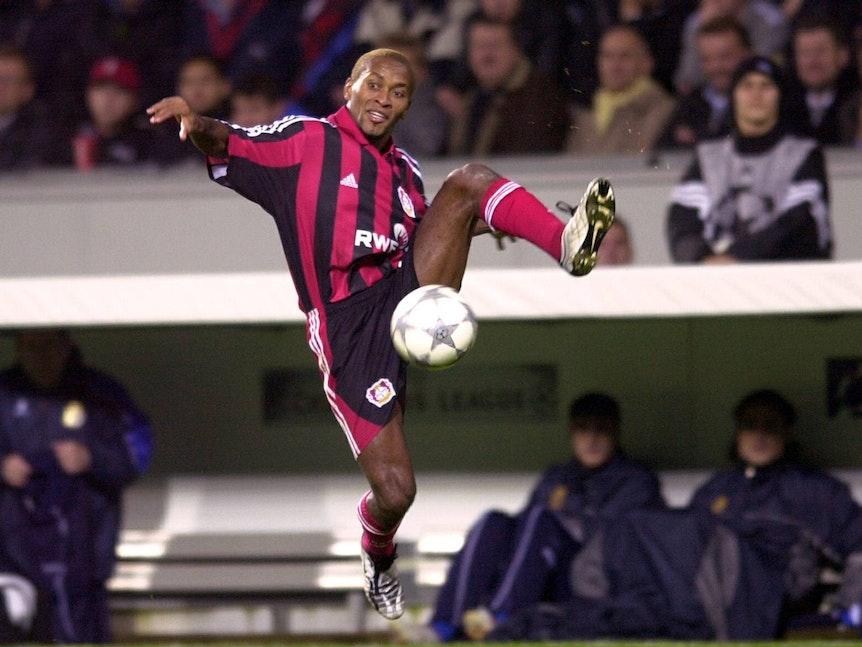 Leverkusens Zé Roberto springt mit gespreizten Beinen zum Ball.