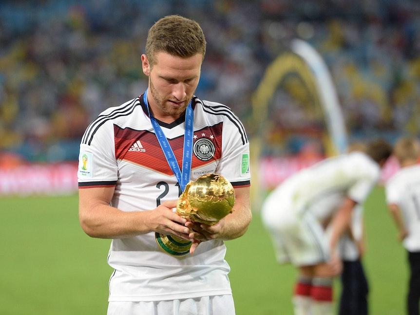 Mustafi schaut sich intensiv den WM-Pokal an.