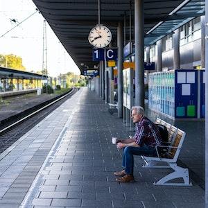 Ein Mann sitzt mit einem Kaffee in der Hand auf einer Bank auf dem ansonsten menschenleeren Bahnsteig.
