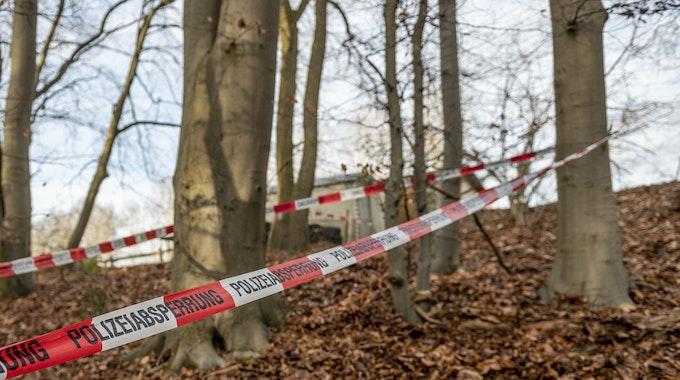 """Ein Flatterband der Polizei ist auf diesem Archivbild vom 17. Januar 2021 in einem Waldstück in Seevetal zu sehen. In einem unzugänglichen Waldstück bei Bonn wurden vor 27 Jahren Knochen gefunden, die Polizei rollt den """"Cold Case"""" nun wieder auf."""
