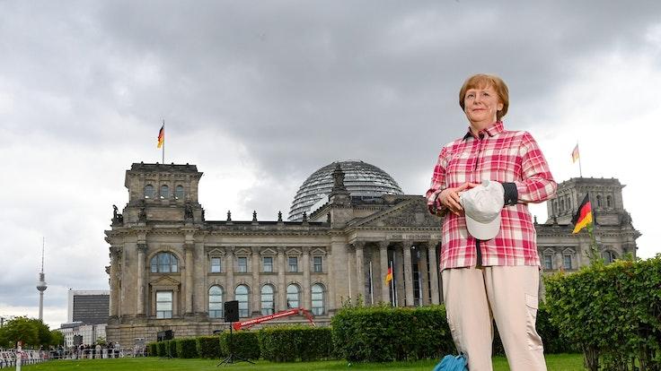 Die Wachsfigur von Bundeskanzlerin Angela Merkel (CDU) aus Madame Tussauds Berlin steht im Freizeitlook mit Rucksack, Basecap vor dem Reichstagsgebäude.