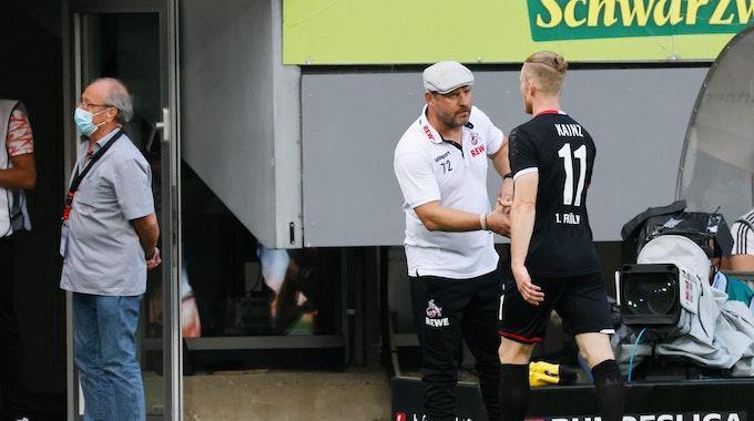 Steffen Baumgart und Florian Kainz vom 1. FC Köln klatschen sich ab.