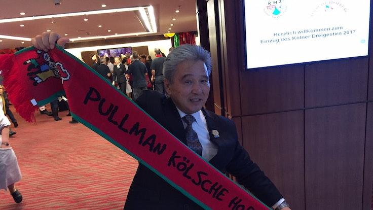 Charly Fukuhara, Barkeeper in der Hofburg, hält einen Schal hoch.