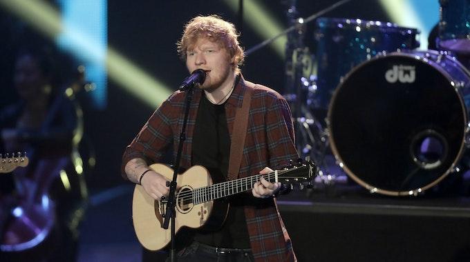 Ed Sheeran singt und spielt Gitarre auf der Bühne.