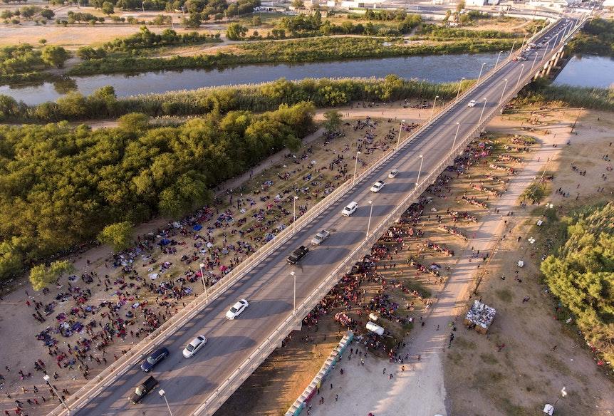 Migranten kampieren unter einer Brücke in Del Rio. Eine Straße ist von oben zu sehen, an der Seite sind unzählige Menschen zu sehen, die dort im Schatten der Brücke verbleiben.