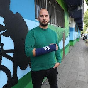 Der Kölner Murat K. (40) zeigt seinen Arm, an den ein Gips angebracht wurde.