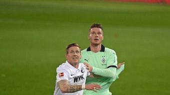 Nico Elvedi (r.), Spieler von Borussia Mönchengladbach und Andre Hahn (l.) blicken im Zweikampf um den Ball nach oben, im Aufeinandertreffen beider Klubs am 12. März 2021.