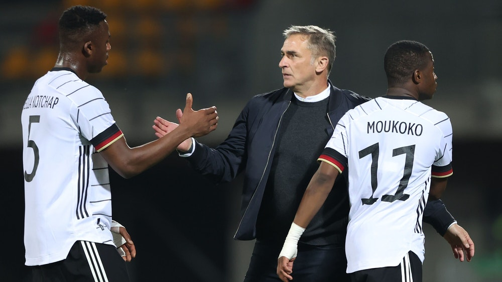 Armel Bella Kotchap (l.) und Youssoufa Moukoko mit U21-Trainer Stefan Kuntz.