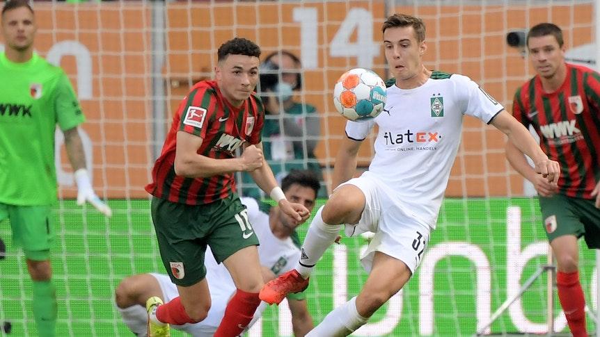 Gladbach-Profi Florian Neuhaus (r.) beim Bundesliga-Spiel in Augsburg am 18. September 2021. In dieser Szene ist Neuhaus im Zweikampf mit Ruben Vargas (l.). Beide Spieler schauen auf den Ball.