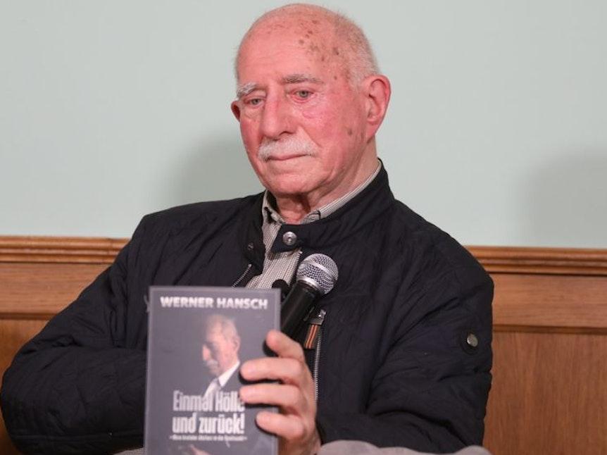 Werner Hansch zeigt sein Buch Einmal Hölle und zurück.