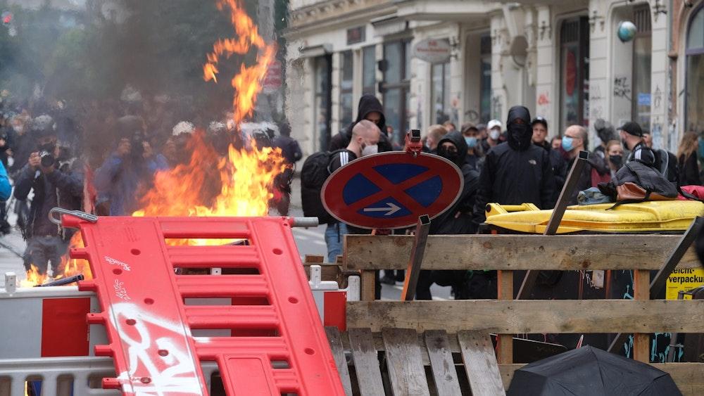18.09.2021, Sachsen, Leipzig: Maskierte Teilnehmer stehen hinter einer Barrikade.
