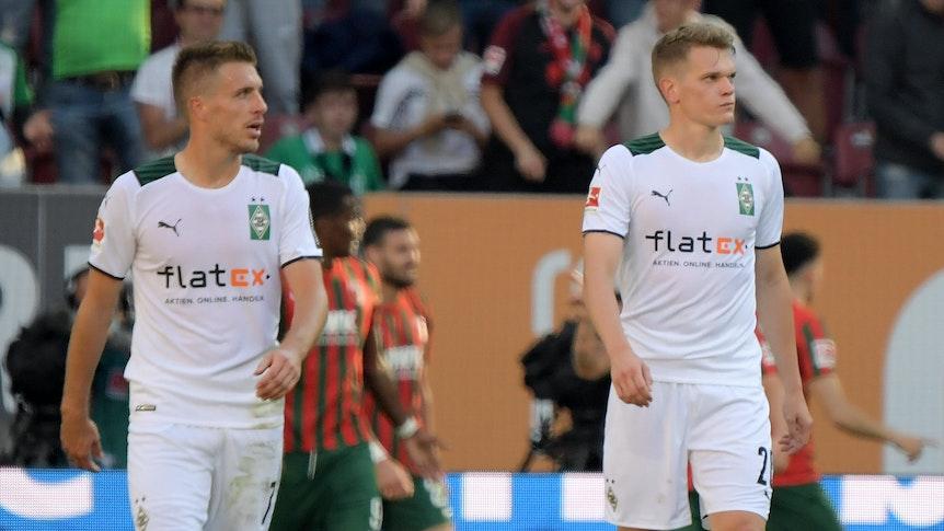 Patrick Herrmann (l.) und Matthias Ginter (r.), Spieler von Borussia Mönchengladbach, gehen mit enttäuschtem Blick vom Platz.
