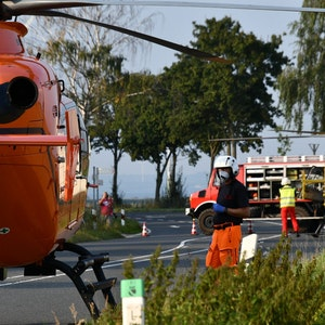 Einsatzkräfte neben zwei Rettungshubschraubern nach dem Unfall in Erftstadt am Samstag (18. September).