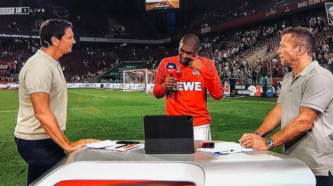 Anthony Modeste weint beim Sky-Interview mit Sebastian Hellmann (l.) und Lothar Matthäus (r.) am 18. September 2021 nach dem 1:1 des 1. FC Köln gegen RB Leipzig.