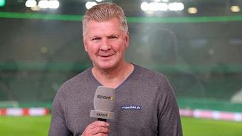 """Ex-Gladbach-Spieler Stefan Effenberg arbeitet als TV-Experte für den Sender """"Sport1"""". Auf diesem Foto ist der ehemalige Nationalspieler am 3. Februar 2021 zu sehen. Effenberg hält das Mikro in der Hand und lächelt in die Kamera."""