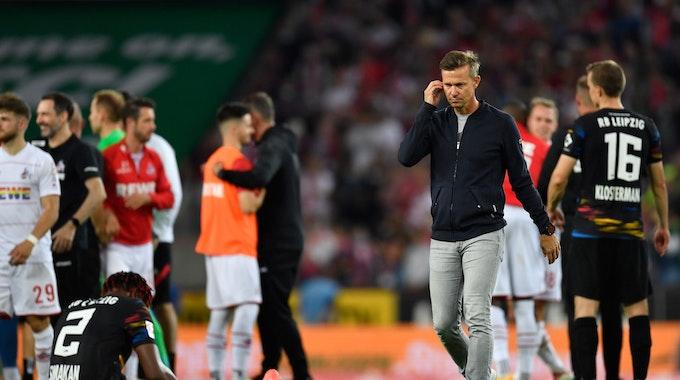 Leipzigs Trainer Jesse Marsch (r) geht nach dem Spiel über den Platz. Links sitzt Leipzigs Mohamed Simakan auf dem Rasen.