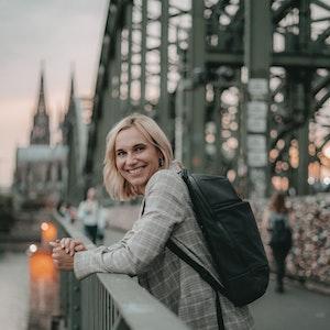 Lena Brabender (26) steht auf einer Brücke, im Hintergrund der Kölner Dom.