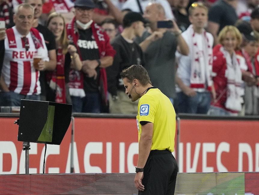 Felix Brych schaut sich bei 1. FC Köln gegen RB Leipzig eine strittige Szene am TV-Bildschirm an.
