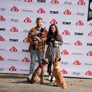 Ein Pärchen steht mit seinen drei Hunden auf der Bühne.