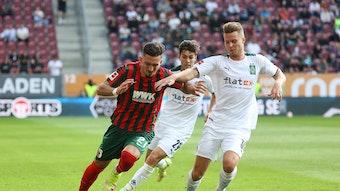 Nico Elvedi, Spieler von Borussia Mönchengladbach im Kampf um den Ball mit Andi Zeqiri vom FC Augsburg am 19. September 2021, dahinter kommt Joe Scally von Gladbach angelaufen.