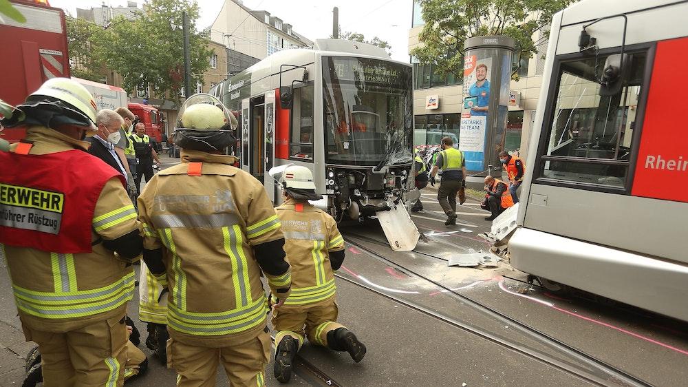 Mitglieder der Feuerwehr sind vor Ort, nachdem zwei Straßenbahnen der Düsseldorfer Rheinbahn am Montag, 20. September 2021, zusammengestoßen sind.