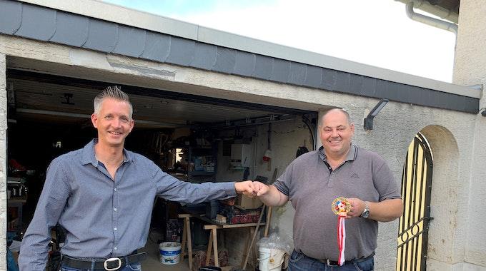 """Stephan Linke (links) macht seinem Kumpel Stefan """"Steff"""" Linden eine Freude und schenkt dem von der Flutkatastrophe hart Getroffenen am 14. September 2021 in Swisttal-Odendorf einen neuen alten EXPRESS-Orden."""