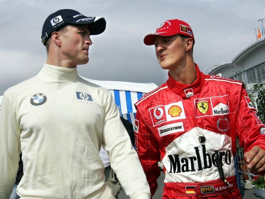 Der deutsche Formel-1-Pilot Ralf Schumacher und sein Bruder Michael unterhalten sich nach dem Qualifikationstraining zum Großen Preis von Japan am 10.10.2004 in Suzuka.
