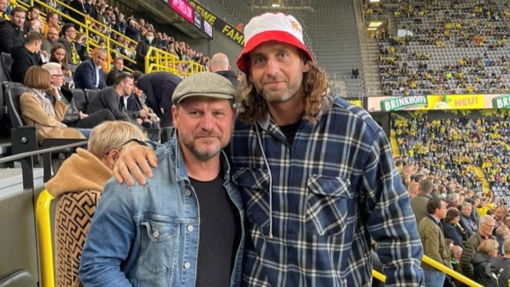 Kölns Trainer Steffen Baumgart mit Handball-Torwart Silvio Heinevetter.