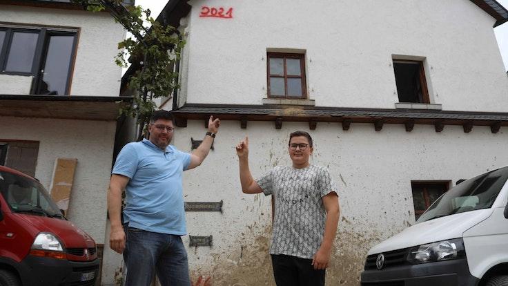 Familie in Dernau zeigt Pegelstand des Hochwassers von Juli 2021