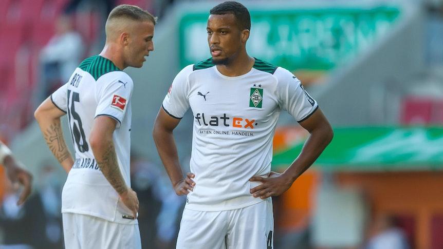 Alassane Plea (l.) und Jordan Beyer (r.) von Borussia Mönchengladbach stehen am 18. September 2021 mit den Händen in den Hüften auf den Fußballplatz und schauen enttäuscht.