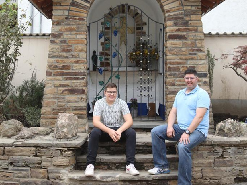 Christian und Arne Schrading sitzen vor der Kapelle an der Hauptstraße in Dernau.