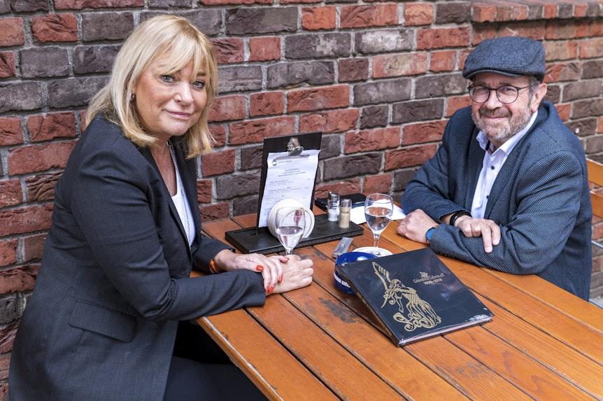 Ursula Brauckmann und Christof Ernst sitzen am Tisch und schauen in die Kamera.