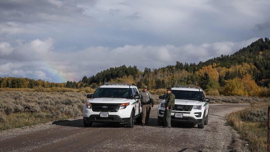 Beamte der U.S. Park Ranger blockieren den Zugang für Fahrzeuge mit zwei SUVs. Sie stehen auf einer Schotterstraße, hinter ihnen ist ein Waldstück zu sehen.