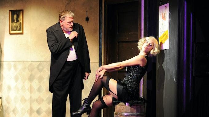 Schauspielerin Katharina Kaali (alias Rosa Fröhlich) singt auf der Bühne in einem aufreizendem Kleid neben Schauspieler Wilfried Dziallas, der einen schwarzen Anzug trägt.