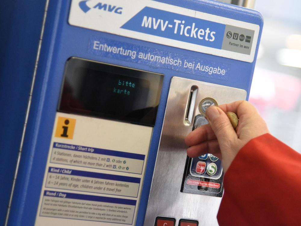 Eine Person wirft Münzen in einen Automaten des Münchner Verkehrs- und Tarifverbunds