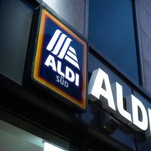 Das Logo einer Aldi Süd Filiale, fotografiert im November 2020 in einer Fußgängerzone der Düsseldorfer Innenstadt. Das Logo leuchtet, es ist Abend.