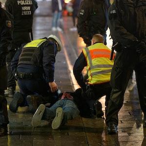 Mitarbeiter des Ordnungsamtes und der Polizei halten am 12. Dezember 2020 in der Düsseldorfer Altstadt einen bei einer Kontrolle Geflüchteten auf dem Boden fest.
