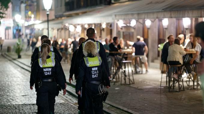 Polizisten patrouillieren am 10. Juli in der Düsseldorfer Altstadt zwischen Feiernden.