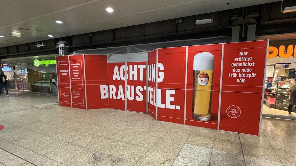 """Ein Bauschild mit der Aufschrift """"Achtung Braustelle"""" steht im Kölner Hauptbahnhof und kündigt das neue Lokal der Brauerei Früh an."""