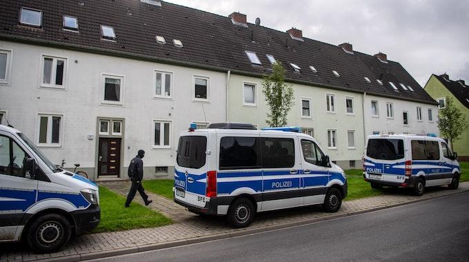 Polizei-Autos vor einem Mehrfamilienhaus.