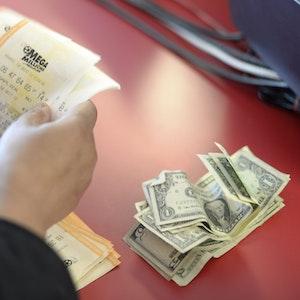 """Unser Symbolfoto zeigt einen Kunden, der Scheine der Lotterie """"Mega Millions"""" im Dezember 2013 erwirbt."""