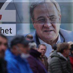Mehrere Zuhörer stehen am 21. September neben einem Wahlkampfbus in Stralsund, um bei einer Wahlkampfkundgebung mit Bundeskanzlerin Angela Merkel und dem CDU-Kanzlerkandidaten Armin Laschet teilzunehmen.