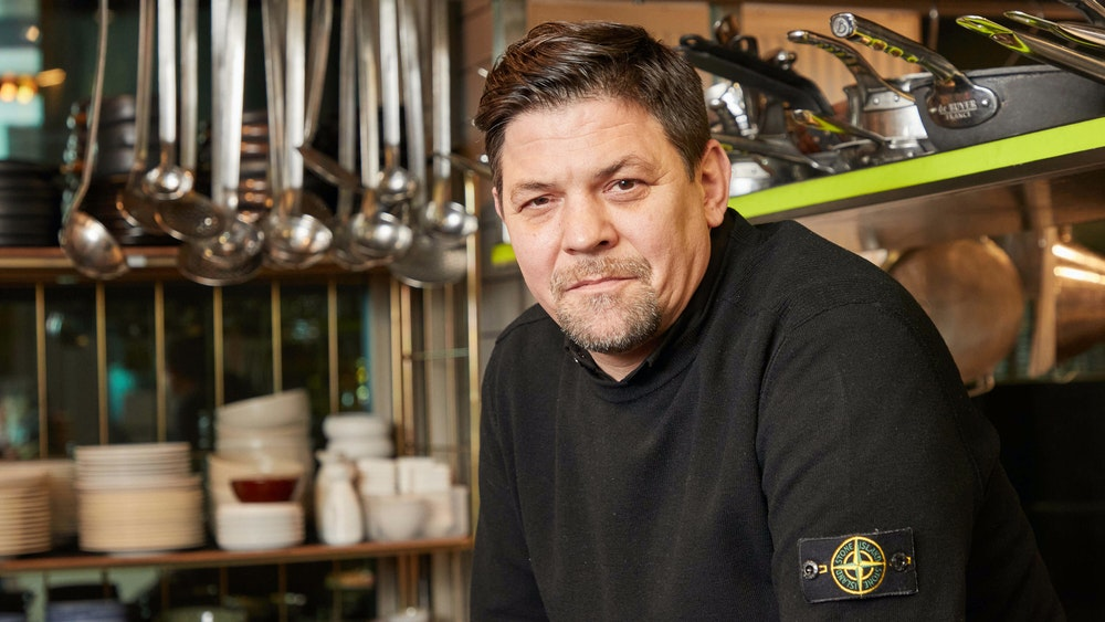"""Fernsehkoch Tim Mälzer sitzt in der Küche seines Restaurants """"""""Die Gute Botschaft""""""""."""