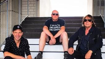 Torsten Knippertz, Stadionsprecher von Borussia Mönchengladbach, hat gemeinsam mit Kurt Schmidt und Pete Brough (v.l.n.r.) sitzen nebeneinander auf einer Treppe, die in den Borussia-Park führt.