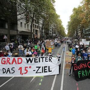 Hinter zwei großen Bannern stehe tausende Demonstranten einer Fridays for Future Demo.