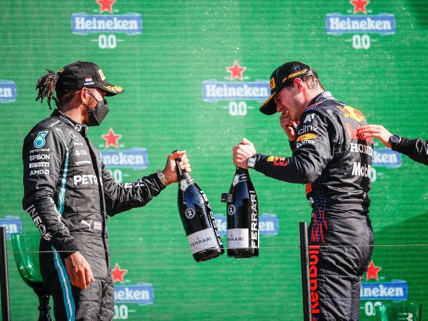 Lewis Hamilton und Max Verstappen stoßen beim Großen Preis der Niederlande auf dem Podium mit Champagner-Flaschen an.