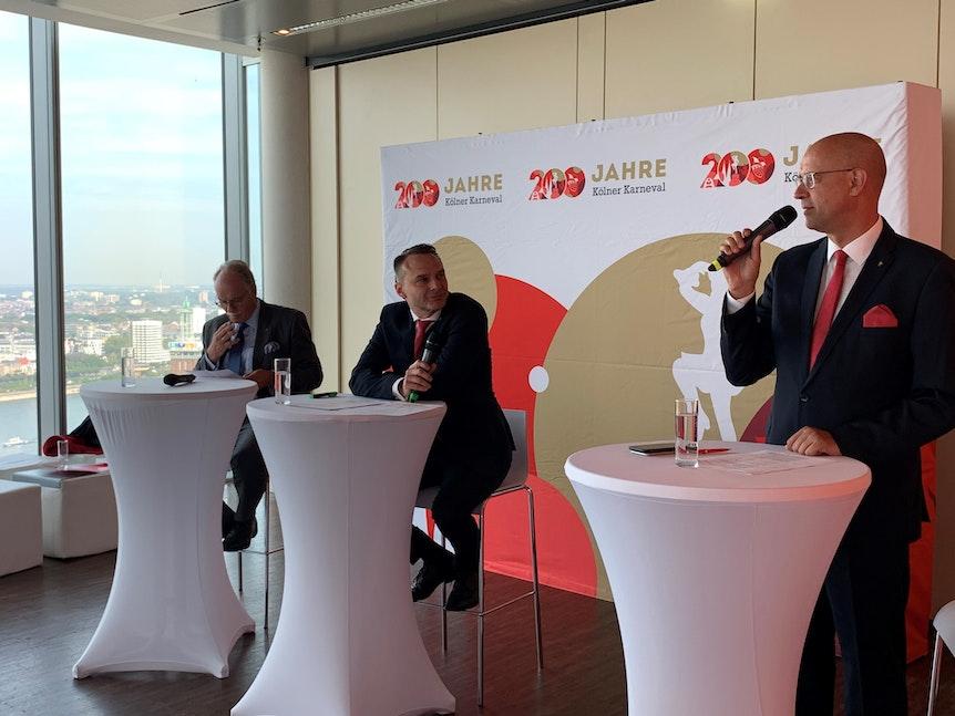 Kölnkongress-Chef Bernhard Conin, Holger Kirsch und FK-Sprecher Michael Kramp (v.l.) stehen an drei Pulten mit Mikrofonen in der Hand