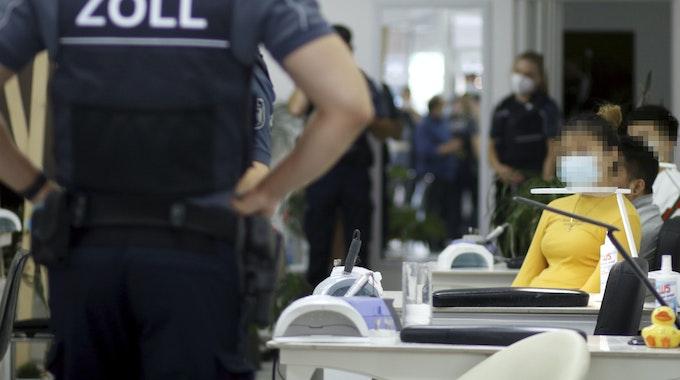 Ein Zollfahnder steht mit den Händen in Hüften in einem Nagelstudio in Köln.