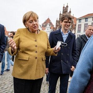 Bundeskanzlerin Angela Merkel (l., CDU) und Georg Günther (CDU), Vorsitzender der Jungen Union Mecklenburg-Vorpommerns, bei einem Überraschungsbesuch auf dem Wochenmarkt von Greifswald. Merkel spricht mit der Blumenhändlerin Edeltraud Honig, es sind schöne Worte des Abschieds.