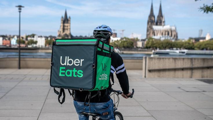 Ein Radfahrer mit großer Essenstasche von Uber Eats auf dem Rücken.